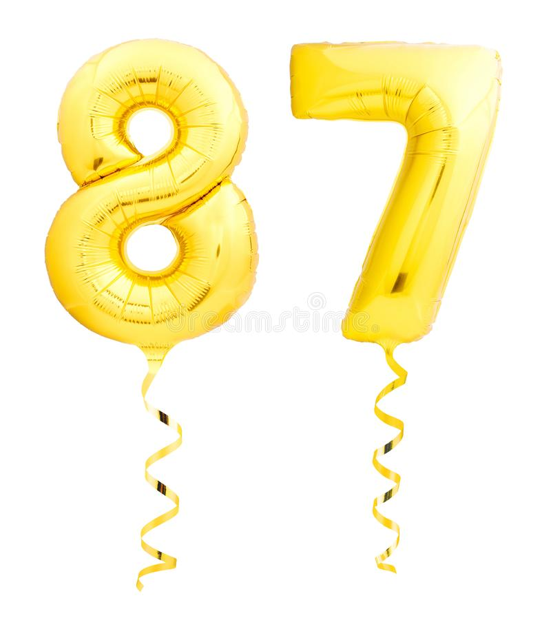 Golden number eighty seven 87 made of inflatable balloon with ribbon on white. Golden number eighty seven 87 made of inflatable balloon with golden ribbon royalty free stock image