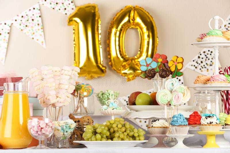 Golden number ten balloon over table with delicious treats at Birthday party stock photos