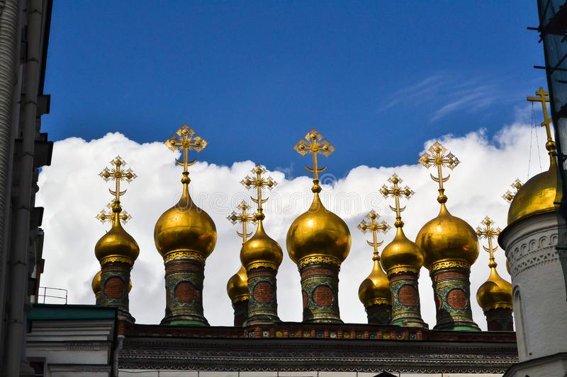 Golden Orthodox crosses and domes of the Church of the Nativity Verkhospasskiy Sobor at Kremlin, Moscow with blue sky stock photo