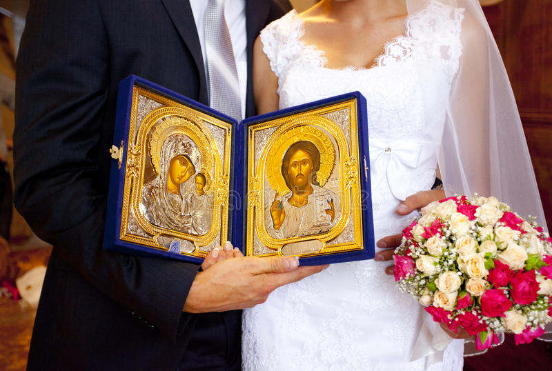 Golden Orthodox icons of The virgin and Jesus in hands of bride and groom royalty free stock images