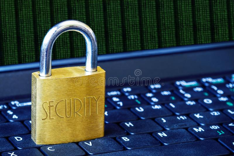 Golden Padlock on Keyboard Cyber Security Concept With Copy Space. Golden padlock on computer laptop keyboard with binary data running and copy space. Concept of stock photography