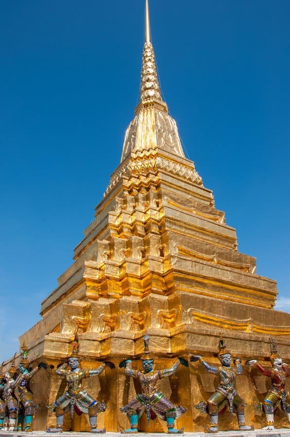 Golden pagoda with guard demon at Royal Palace, Bangkok, Thailand. royalty free stock image