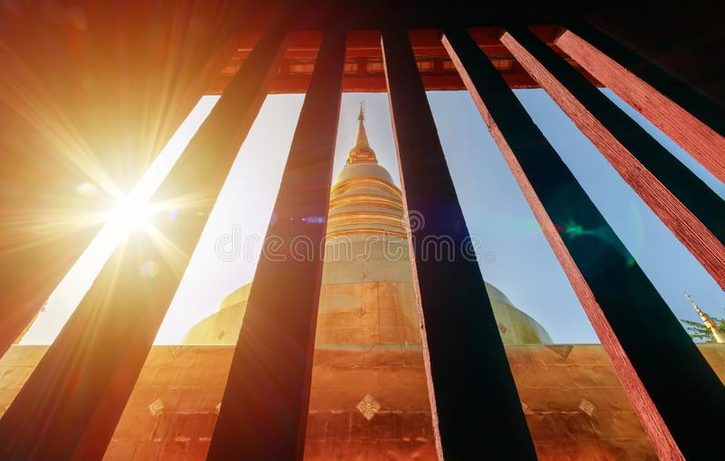 Golden pagoda view from vintage window at Wat Phra Singh in Chiang Mai, Thailand with light flare in the morning. Travel destination landmark royalty free stock photography