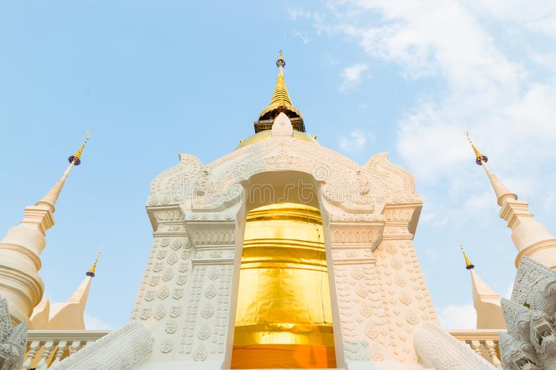 The golden pagoda at Wat Suan Dok, Chiangmai, Thailand. The beautiful pagoda in contrasted with beautiful blue sky and clouds.  stock photography