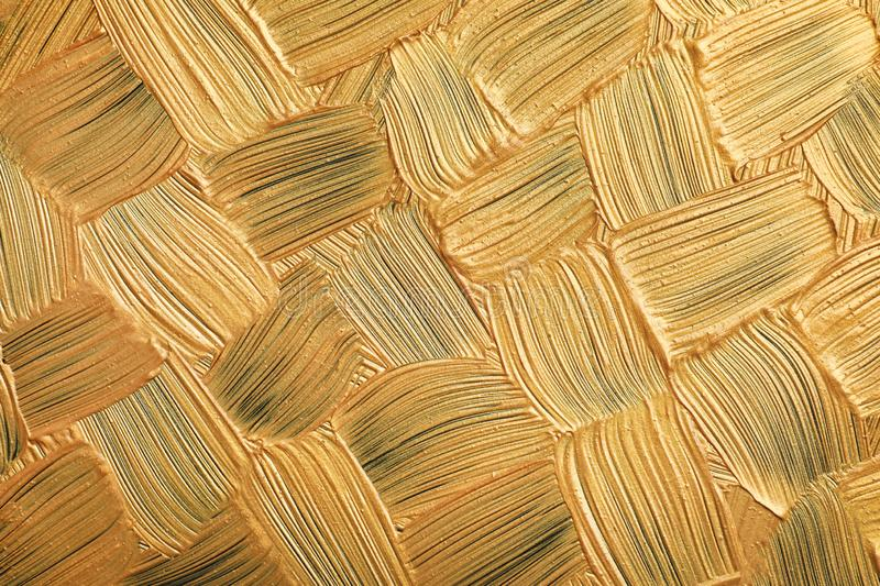 Golden paint brush strokes as background. Closeup stock image