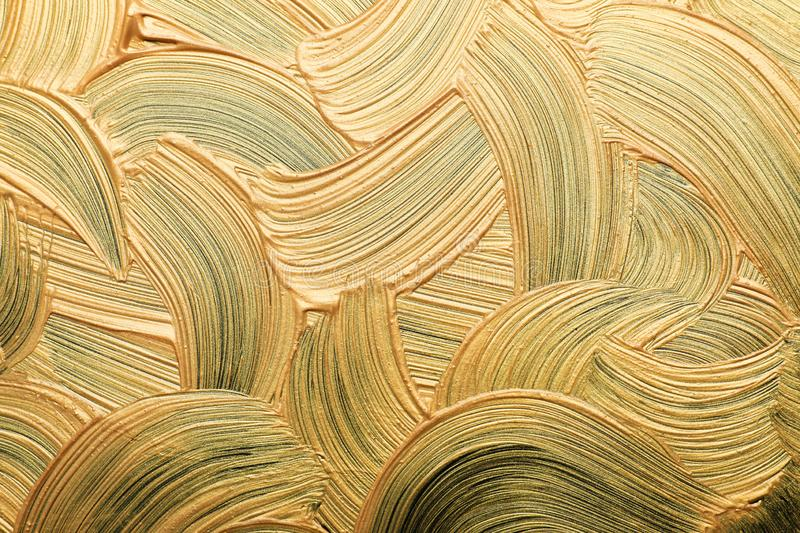 Golden paint brush strokes as background. Closeup stock photography