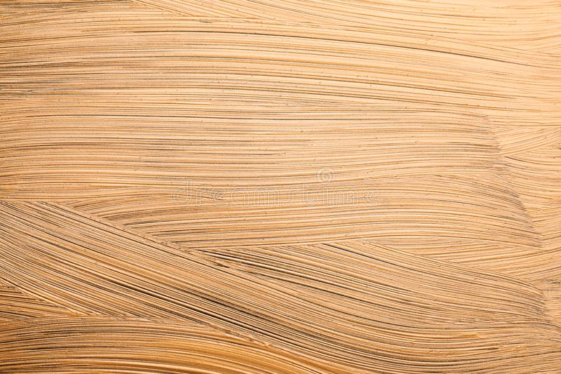 Golden paint brush strokes as background. Closeup royalty free stock photo