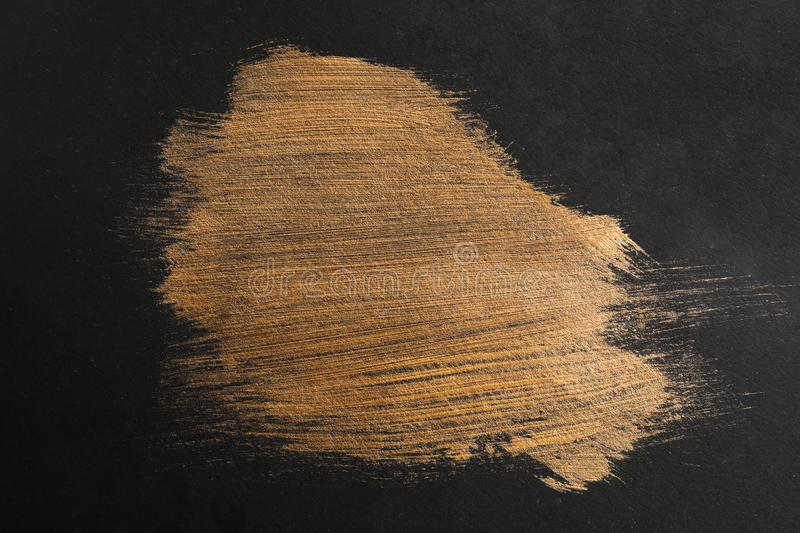 Golden paint brush strokes on black. Background royalty free stock photography