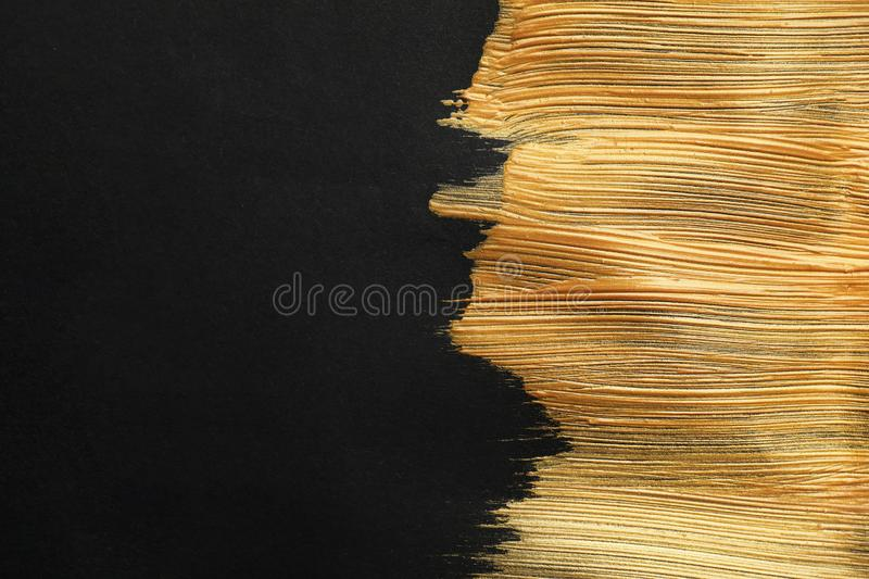 Golden paint brush strokes on black background. Space for text royalty free stock photos