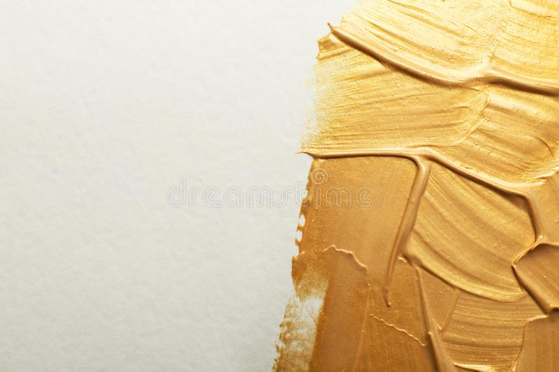 Golden paint brush strokes on white background. Space for text stock photography