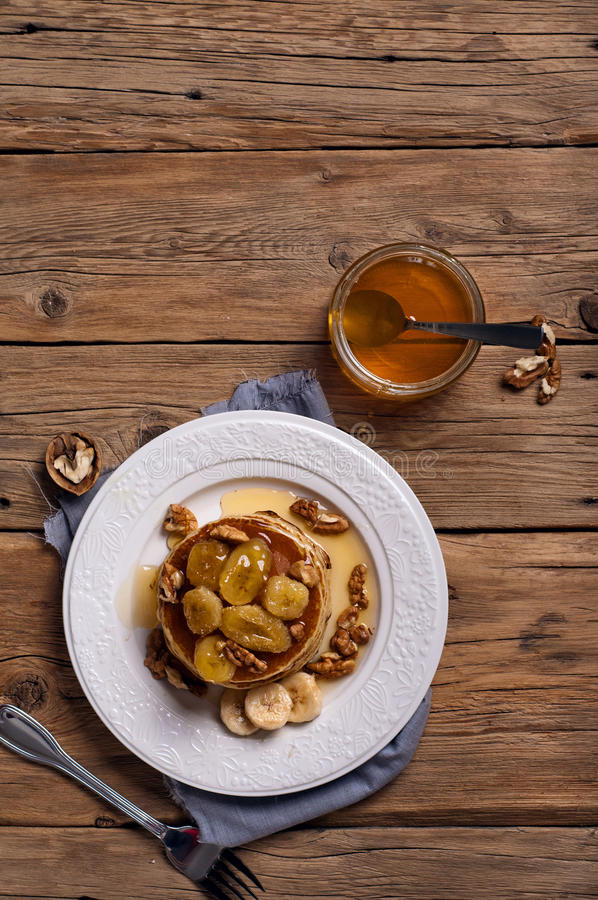 Golden pancake with caramelized bananas, honey and nuts stock photography