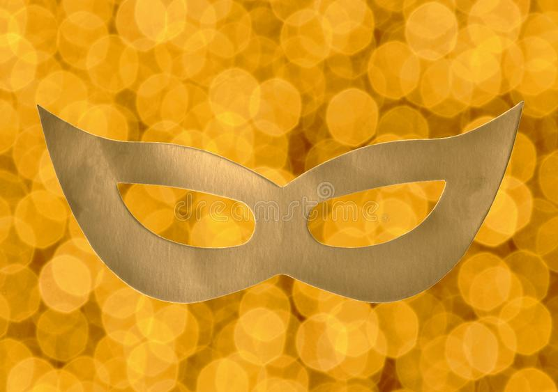 Golden paper mask on yellow blurry electric light background stock photography