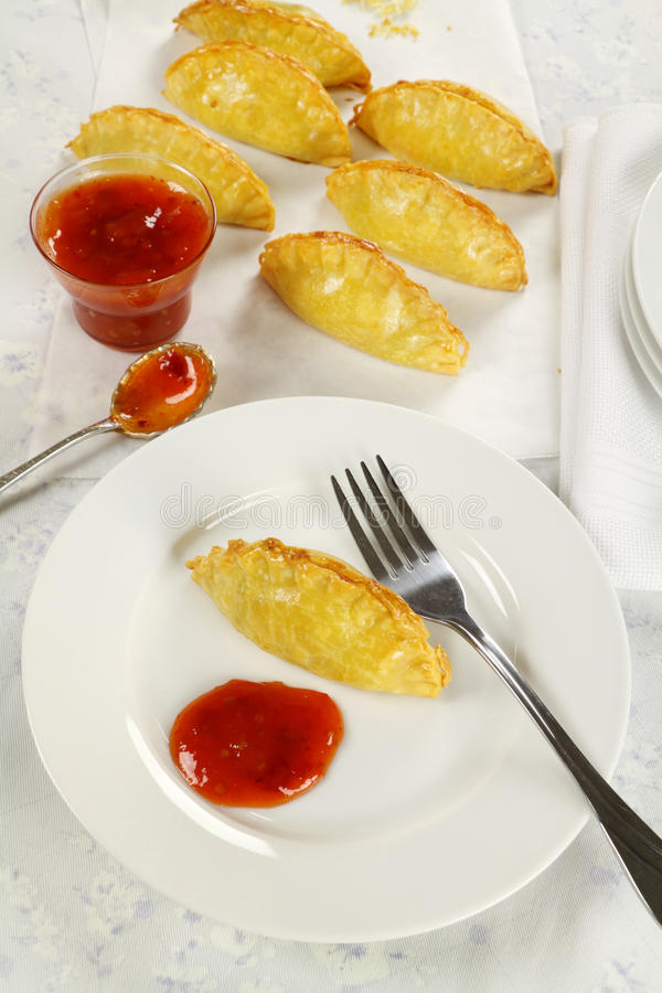 Golden Pasties. Delicious fresh baked golden pasties with sweet chili relish royalty free stock photos