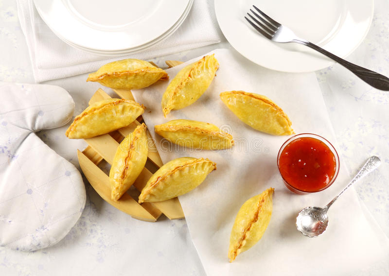 Golden Pasties. Delicious fresh baked golden pasties with sweet chili relish stock photo