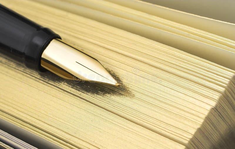 Golden pen on golden agenda stock image