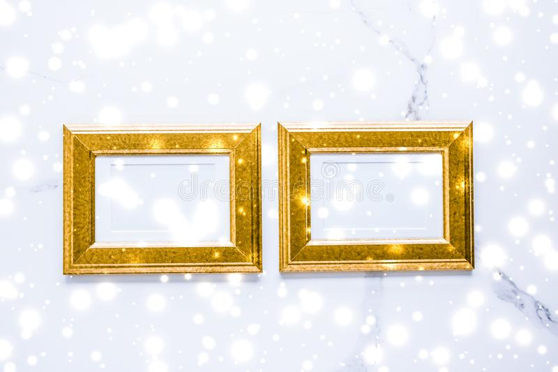 Golden photo frame and glowing glitter snow on marble flatlay background for Christmas and winter holidays stock image