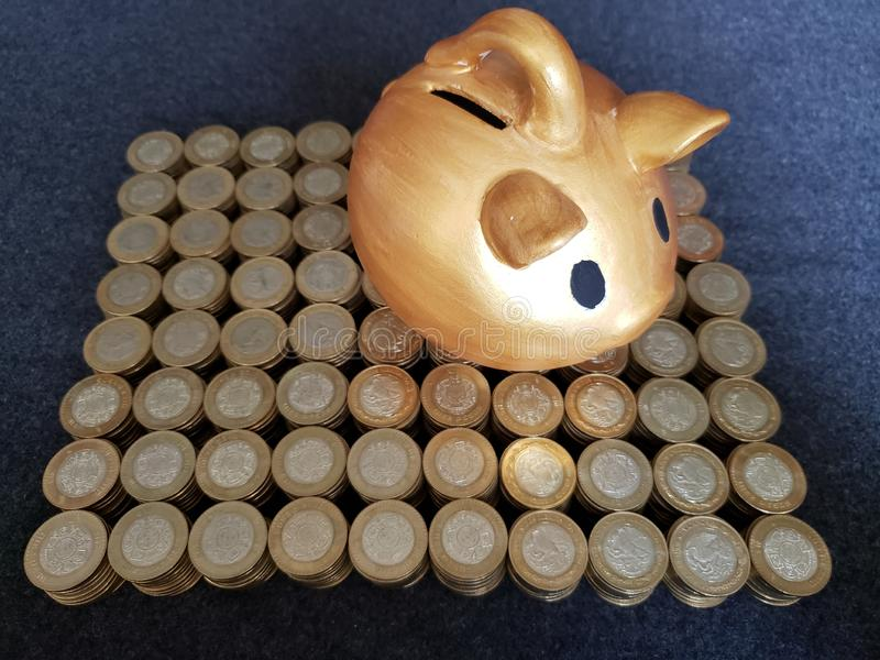 Golden pig piggy bank and stacked coins of mexican pesos. Trading and exchange, bank and commerce, price of buy and sell, cash value and money, economy and stock images