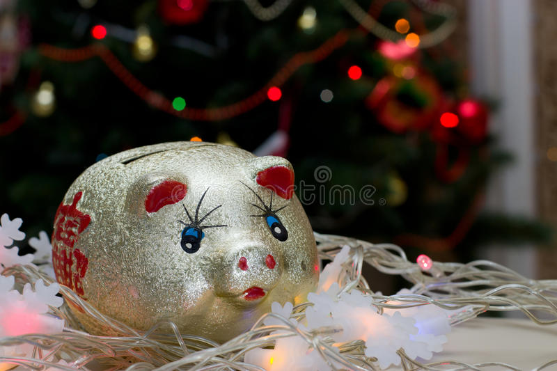 Golden piggy bank with Chinese character. Background - the lights of the Christmas tree stock image