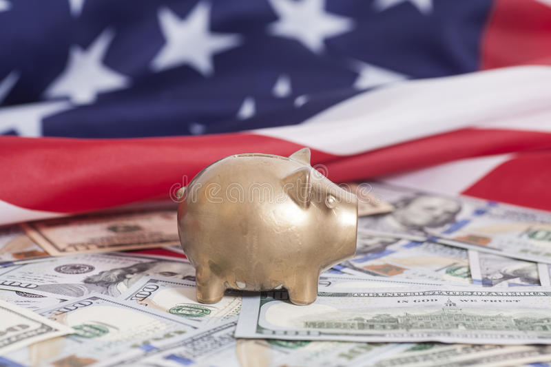 Golden Piggy Bank on Dollars with American Flag royalty free stock photography