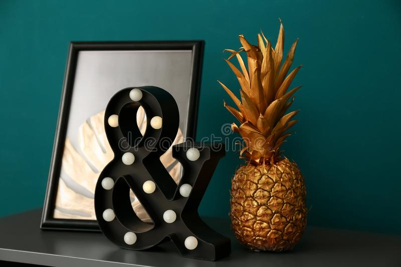 Golden pineapple with stylish decor on table near color wall royalty free stock photography