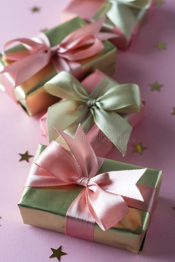 Golden and pink gift box isolated on pink background. Birthday, beauty party concept royalty free stock images