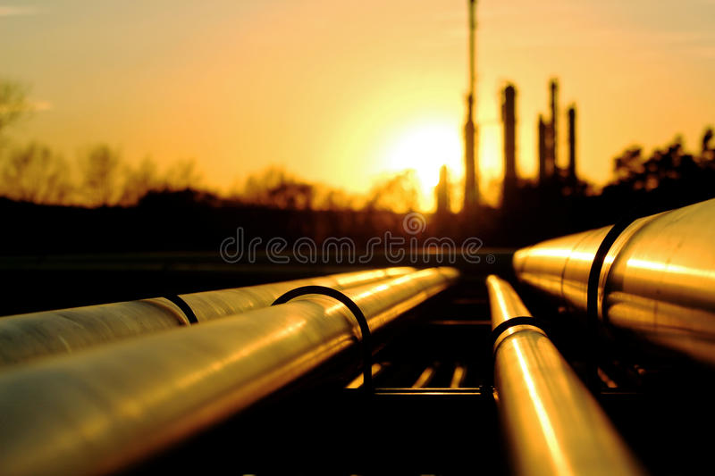 Golden pipes going to the oil refinery royalty free stock photography