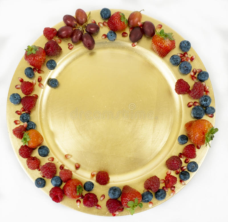 Golden plate with seasonal fresh fruit with space for copy. stock photo