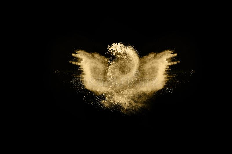 Golden powder explosion on black background. Freeze motion. Golden powder on black background,abstract powder splatted on black background,Freeze motion of stock photos