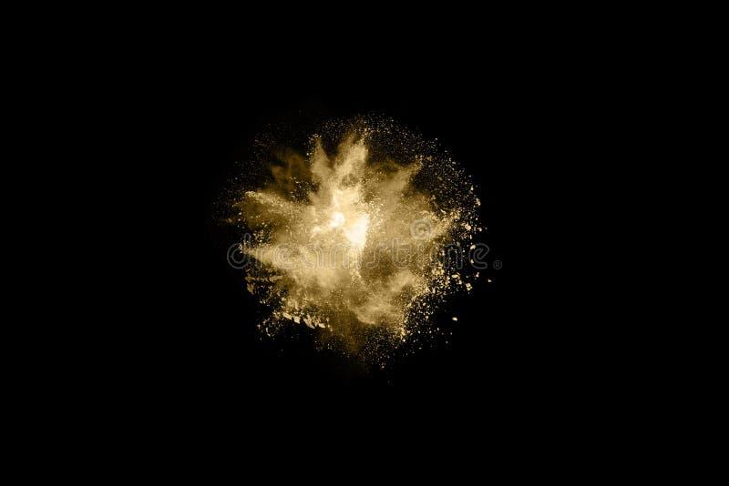 Golden powder explosion on black background. Freeze motion. Golden powder on black background,abstract powder splatted on black background,Freeze motion of stock photo