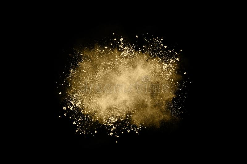 Golden powder explosion on black background. Freeze motion. Golden powder on black background,abstract powder splatted on black background,Freeze motion of royalty free stock photos