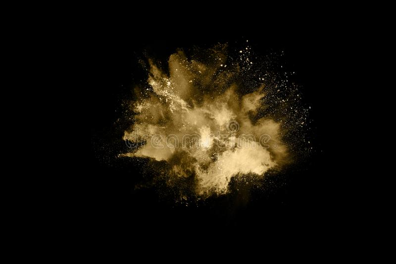 Golden powder explosion on black background. Freeze motion. Golden powder explosion on black  background. Colored cloud. Colorful dust explode. Paint Holi stock image