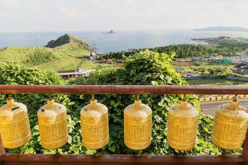 Golden prayer wheels with dragon head at Sanbanggulsa temple, Sanbang-ro, Jeju Island, South Korea stock image