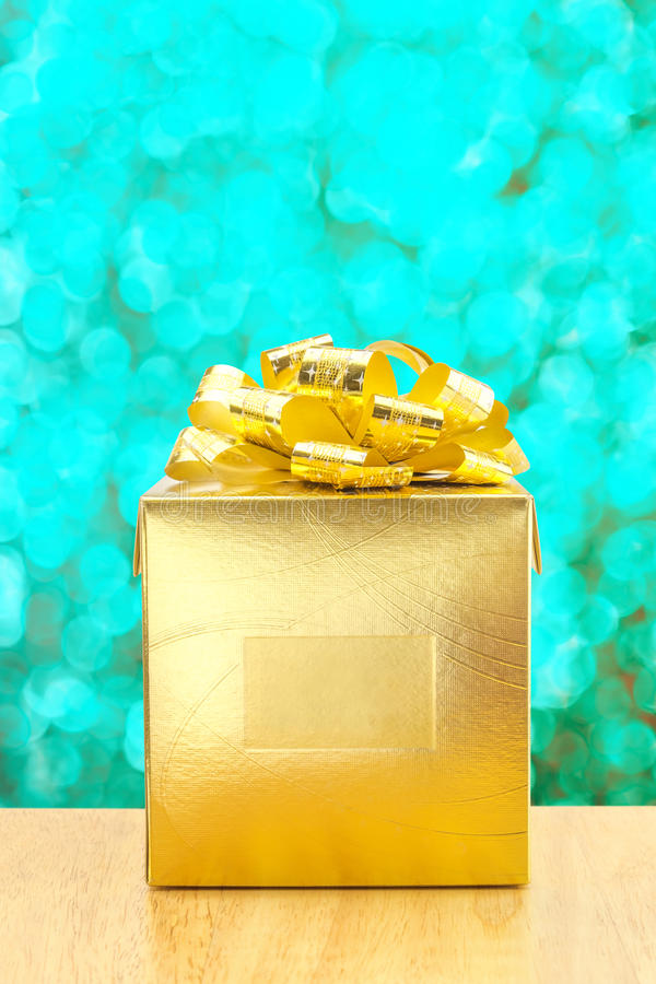 Golden Present box at green bokeh light background, Leave space. For adding your text stock images