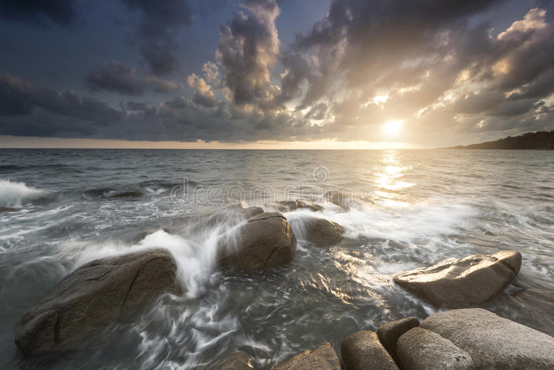 Golden rays of rising sun light up the sea waves at beautiful rocky beach stock photography