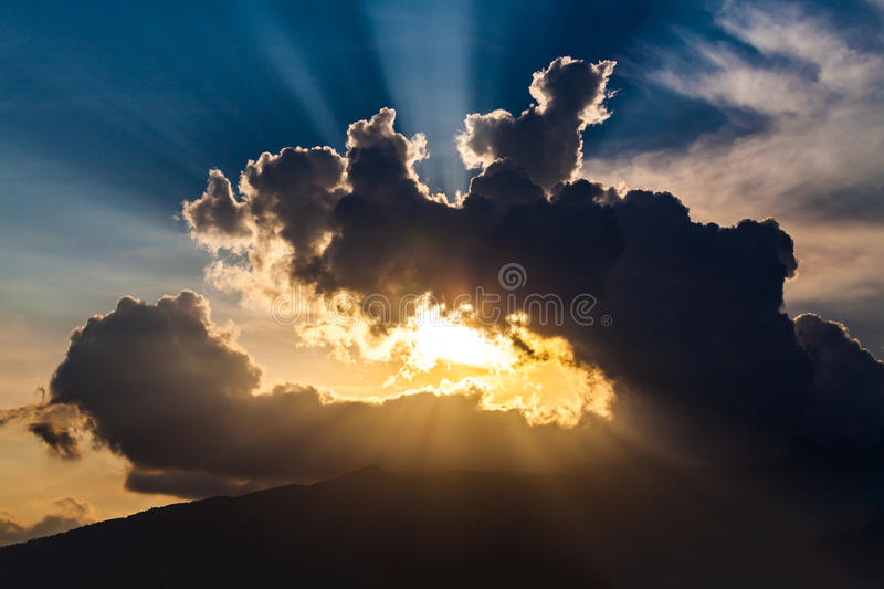 Golden rays of the sun through the black clouds royalty free stock images
