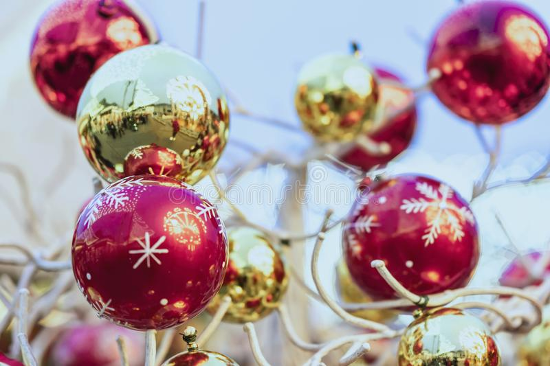 Golden and red Christmas balls with street reflections hanging on decorative wooden tree outdoor. Abstract festive stock images