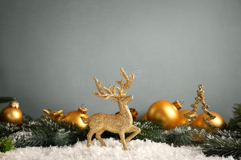 Golden reindeer with Christmas decorations on grey background royalty free stock image