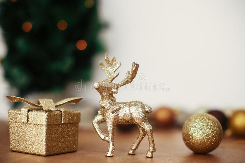 Golden reindeer, gift box and glitter bauble toys on background of christmas tree with lights on rustic background. Merry stock photo