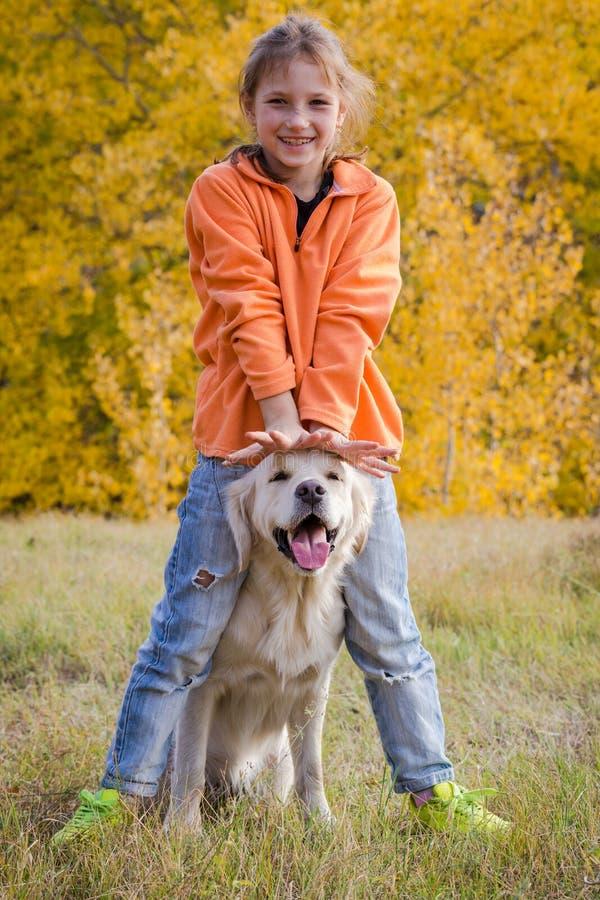 Golden retriever, das auf Feld mit Mädchen spielt lizenzfreie stockbilder
