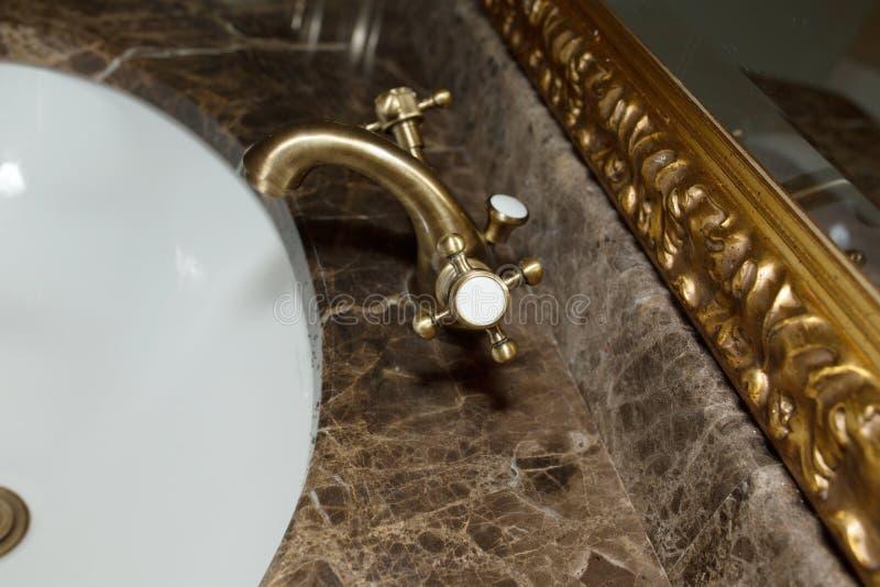 Golden vintage tap in a marble sink. Golden retro tap in a marble sink. Closeup shot stock image
