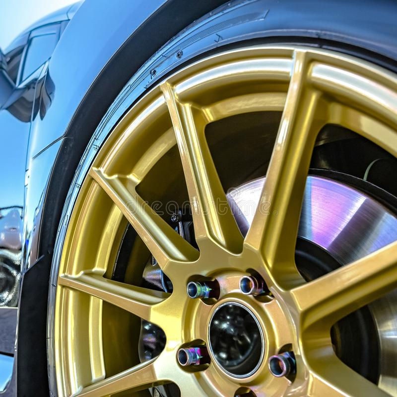 Golden rim with brake pad showing between spokes. Close up of a shiny black car`s golden tire rim. The brake pad can be seen between the radial spokes of the royalty free stock photos
