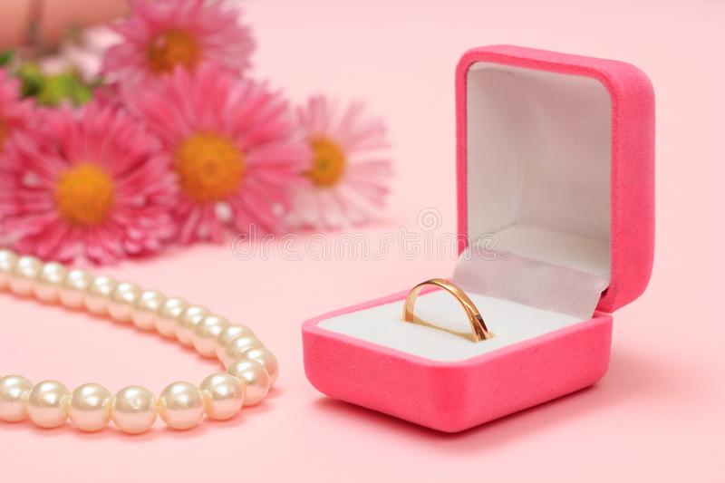 Golden ring in box, beads and flowers on a pink background. royalty free stock images