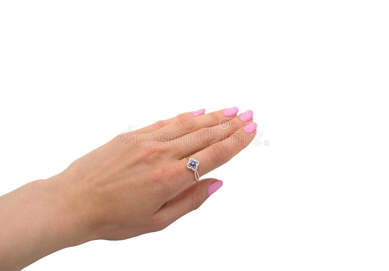 Golden ring with sapphire and diamonds on woman`s hand stock photography