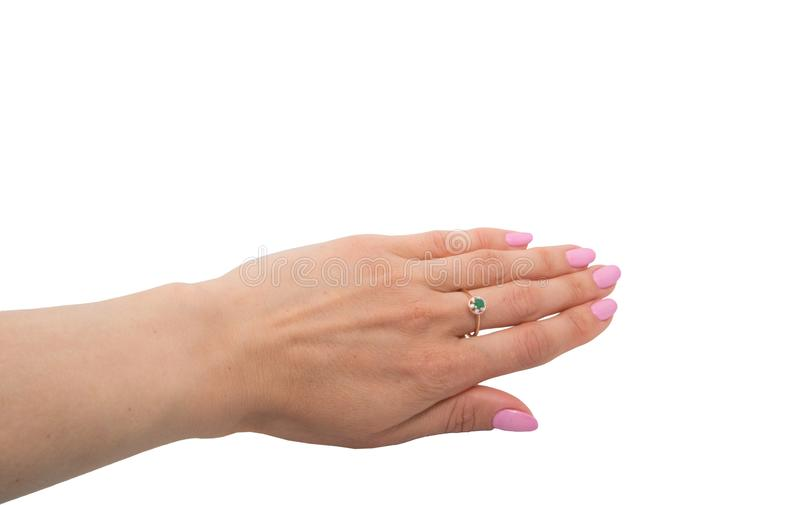 Golden ring with emerald and few diamonds on woman`s finger stock photo