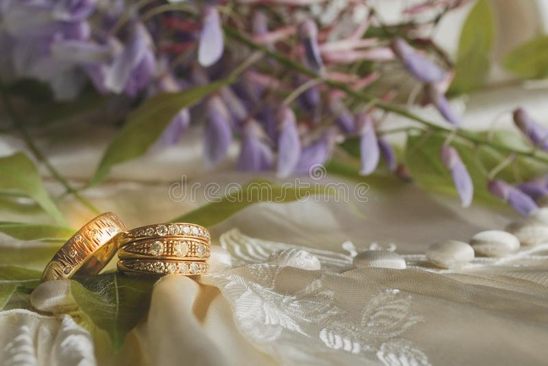 Golden Rings on Antique Ivory Wedding Dress. Two glowing gold rings on antique wedding dress with lavender wisteria stock images