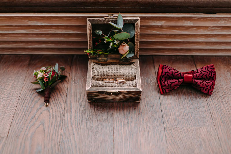 Golden rings in the beautiful rustic box and stylish men wedding accessories on the wooden background. Preparation for wedding concept. Horizontal royalty free stock image