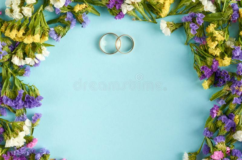 Golden rings with colored flowers on blue background composition, wedding template. Flat lay and top view photo, love, circle, border, frame, leafs, layout royalty free stock photography