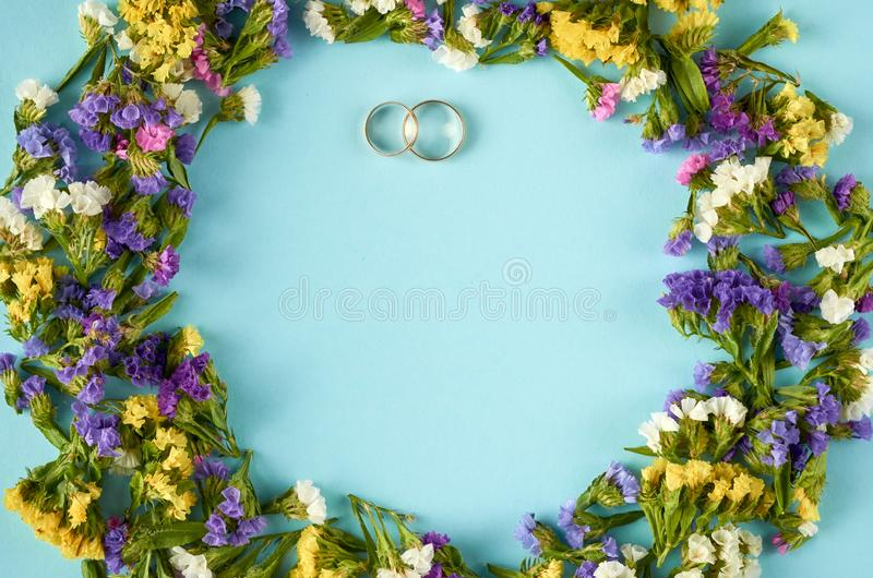 Golden rings with colored flowers on blue background composition, wedding template. Flat lay and top view photo, love, circle, border, frame, leafs, layout stock photography