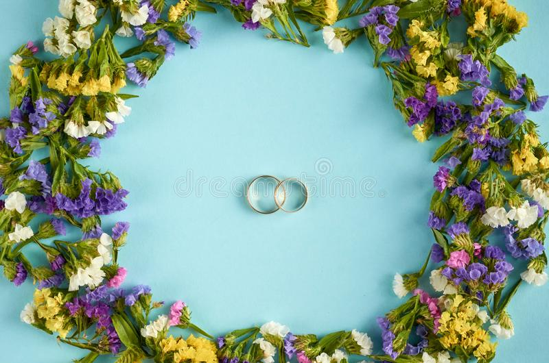 Golden rings with colored flowers on blue background composition, wedding template. Flat lay and top view photo, love, circle, border, frame, leafs, layout royalty free stock images