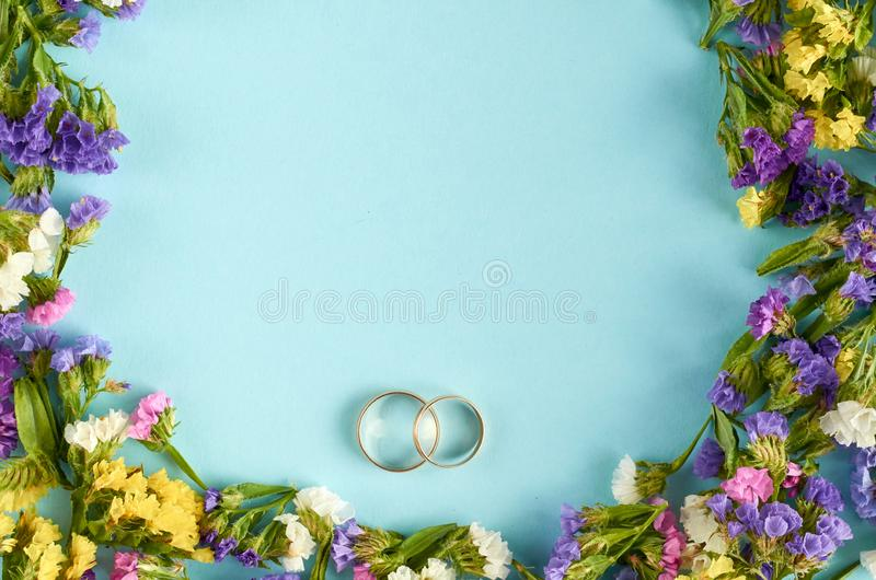 Golden rings with colored flowers on blue background composition, wedding template. Flat lay and top view photo, love, circle, border, frame, leafs, layout royalty free stock photo